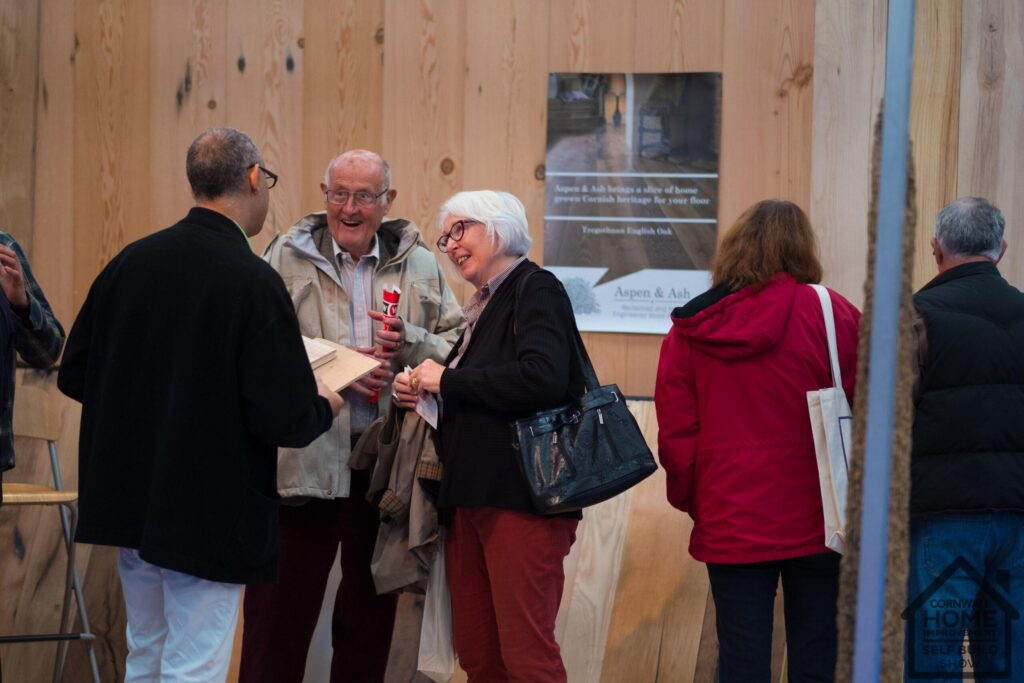 Happy visitors at Cornwall Home Improvement & Self Build Show discussing walling solutions