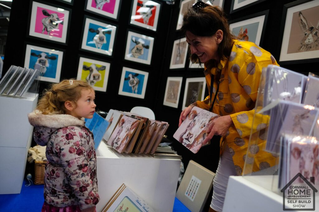 A child and home show exhibitor showing her art for sale at the interiors market