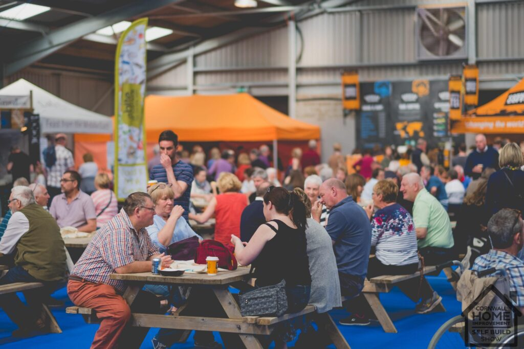 A happy crowd of visitors sat down eating at A Bite of Cornwall Food & Drink Market at Cornwall Home Improvement & Self Build Show