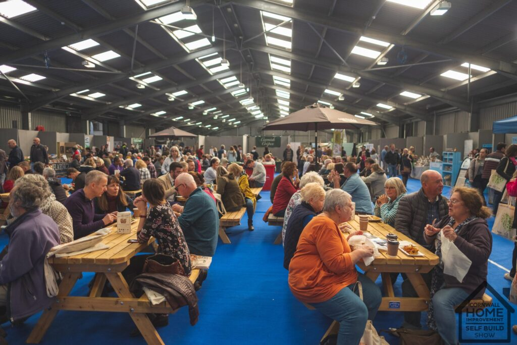 Crowds of people sit and enjoy A Bite of Cornwall food and drink market at Cornwall Home Improvement & Self Build Show