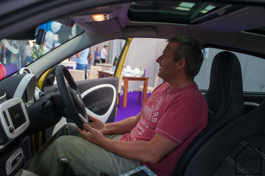 A Cornwall Home Improvement & Self Build Show visitor sitting in an exhbition vehicle
