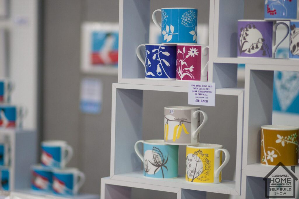 A selection of coloured illustrated mugs at the Interiors Market